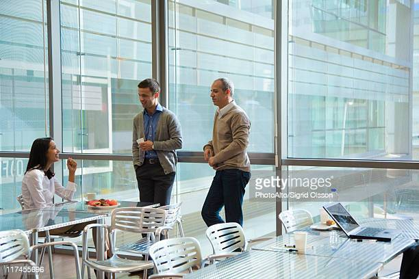 Colleagues talking in office cafeteria
