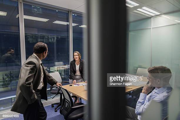 Colleagues talking in office meeting room at night