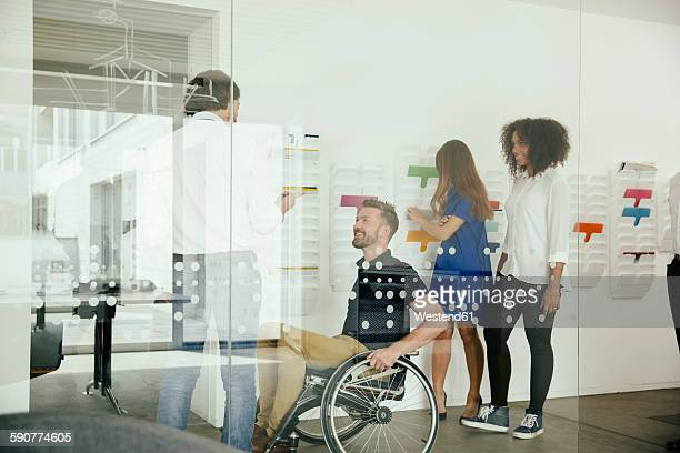 Colleagues talking in office with one sitting in wheelchair