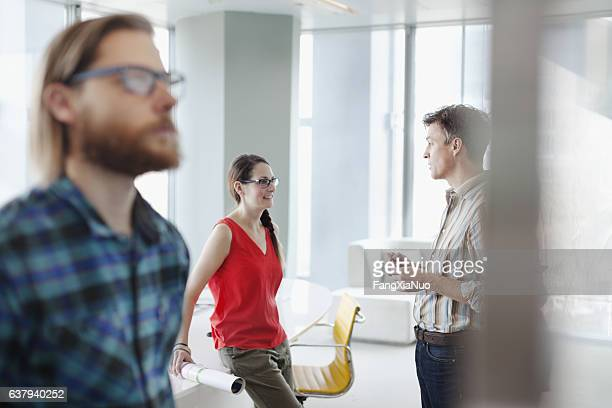 Colleagues talking together in bright office meeting room