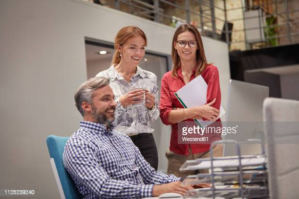 colleagues talking together in in front of pc - employee appreciation stock pictures, royalty-free photos & images