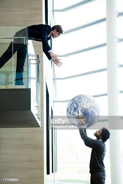 Colleagues throwing ball in lobby
