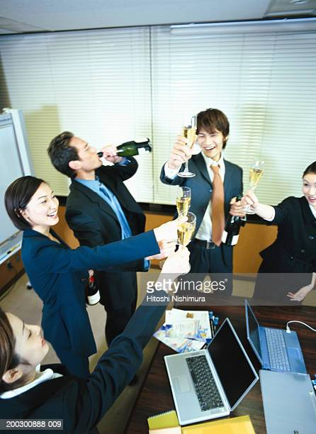 Colleagues toasting in office, elevated view