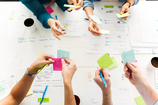 Colleagues using adhesive notes during business meeting - gettyimageskorea