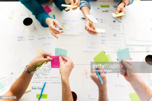 colleagues using adhesive notes during business meeting - brainstormen stockfoto's en -beelden