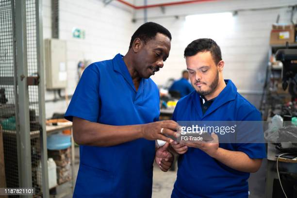 colleagues using digital tablet and working in industry - persons with disabilities stock pictures, royalty-free photos & images