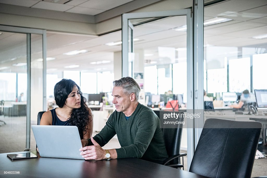 Colleagues using laptop in modern office : Stock Photo