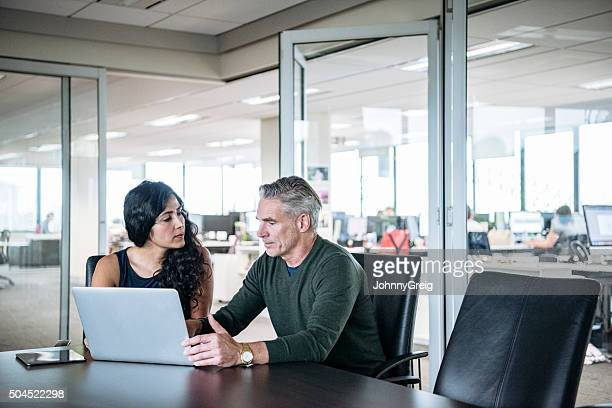 Colleagues using laptop in modern office