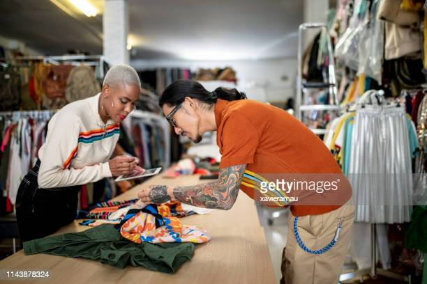 colleagues using tablet pc while checking textile - fashion designer stock pictures, royalty-free photos & images