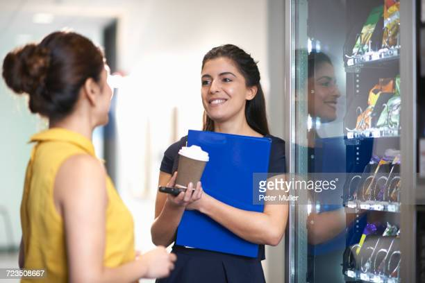 colleagues using vending machine chatting - vending machine stock photos and pictures