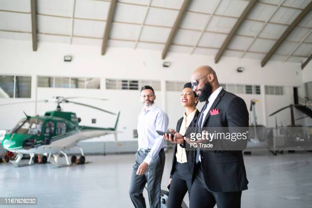 colleagues walking in airplane hangar - best sunglasses for bald men stock pictures, royalty-free photos & images