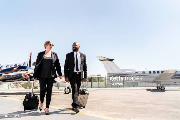 colleagues walking in airport runway - best sunglasses for bald men stock pictures, royalty-free photos & images