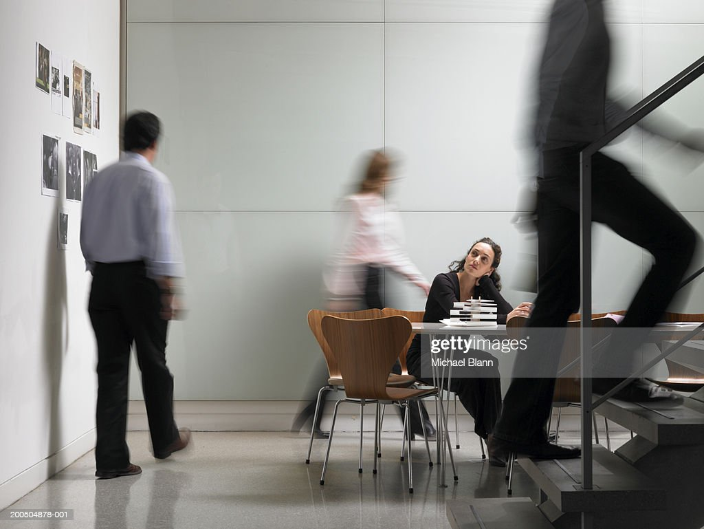 Colleagues walking in board room, woman sitting at conference table : Stock Photo