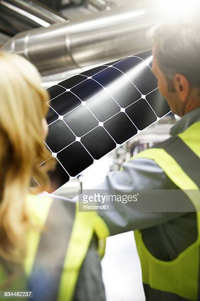 Colleagues wearing reflective vests examining innovative solar panel