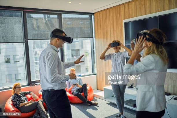 colleagues wearing vr glasses in office - groupe moyen de personnes photos et images de collection
