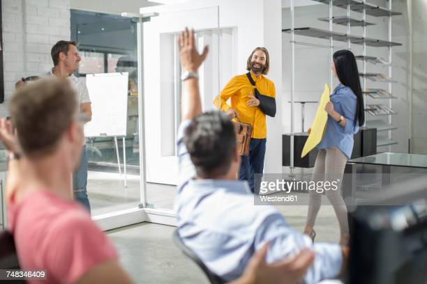 colleagues welcoming injured friend back - arm sling stock pictures, royalty-free photos & images