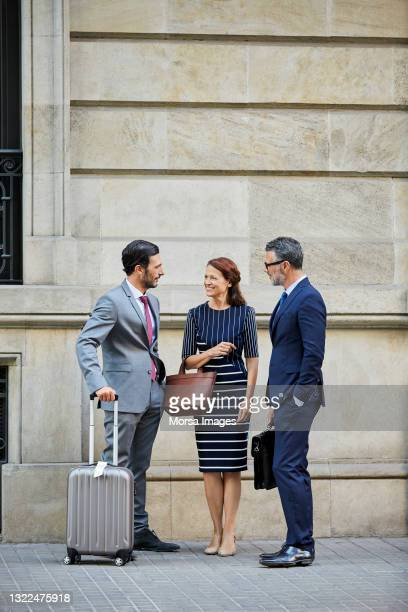 colleagues with luggage discussing outside hotel - 南ヨーロッパ民族 ストックフォトと画像