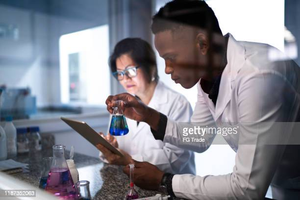 colleagues working and using digital tablet in laboratory - microbiologist stock pictures, royalty-free photos & images