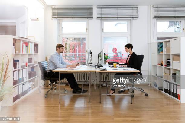 Colleagues working at desk in office