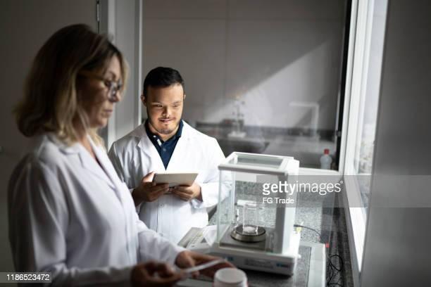 colleagues working in a laboratory - pessoas com deficiência imagens e fotografias de stock