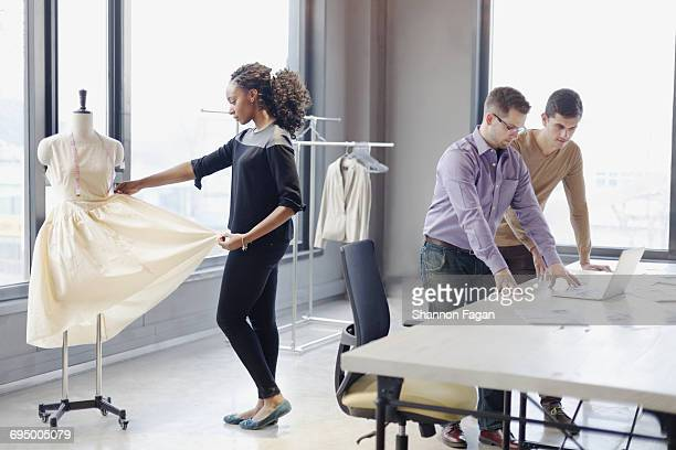 Colleagues working in fashion design studio office