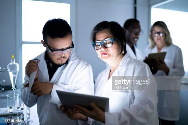 colleagues working in laboratory - pessoas com deficiência imagens e fotografias de stock