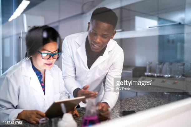 colleagues working in laboratory - medical research stock pictures, royalty-free photos & images