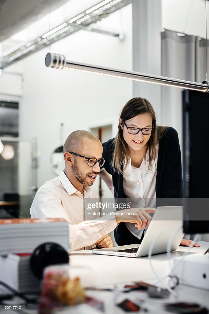 Colleagues working late in modern office : Stock Photo