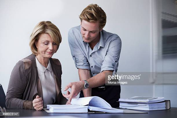 colleagues working on documents - rolled up sleeves stock pictures, royalty-free photos & images