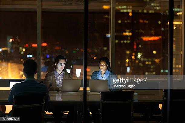 Colleagues working on laptops at night in office