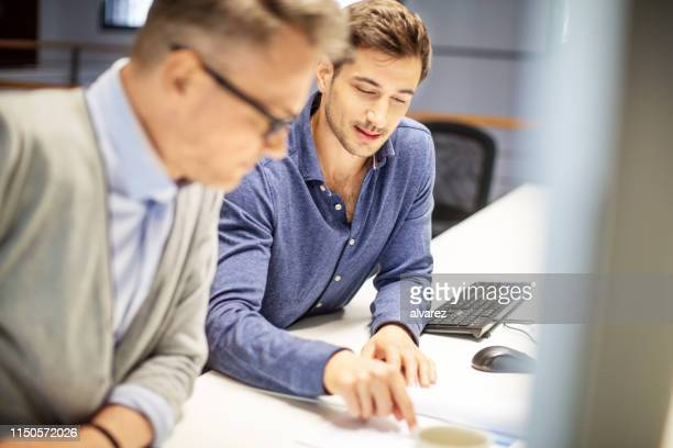 colleagues working over some finance reports - employee engagement stock pictures, royalty-free photos & images