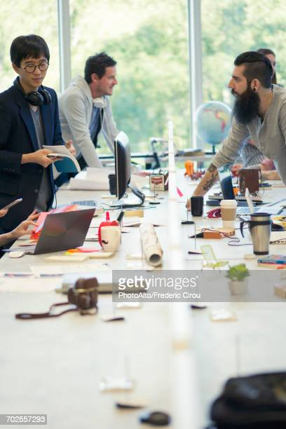 Colleagues working together in open plan office
