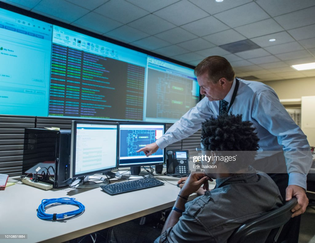 Colleagues working together in server control room : Stock Photo