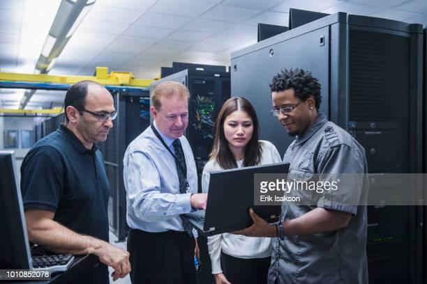 colleagues working together in server room - data center stock-fotos und bilder