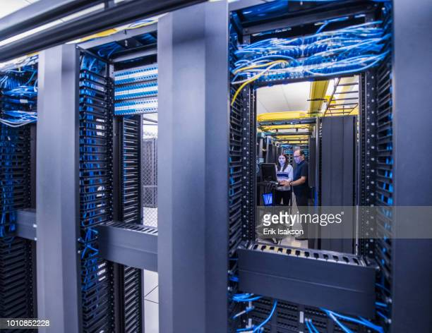 colleagues working together in server room - data center stock pictures, royalty-free photos & images
