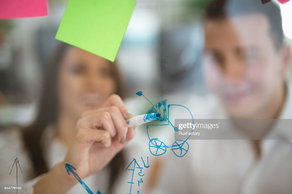 Colleagues writing baby stroller on a glass board : Stock Photo