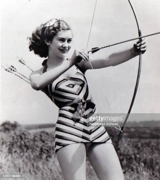 Collectible tobacco card published in 1939 by Ardath Cigarettes, depicting Hollywood cinema star starlet Dinah Sheridan practicing archery wearing a...