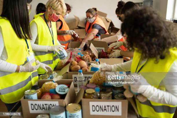 collecting food for donation in a homeless shelter - giving tuesday stock pictures, royalty-free photos & images