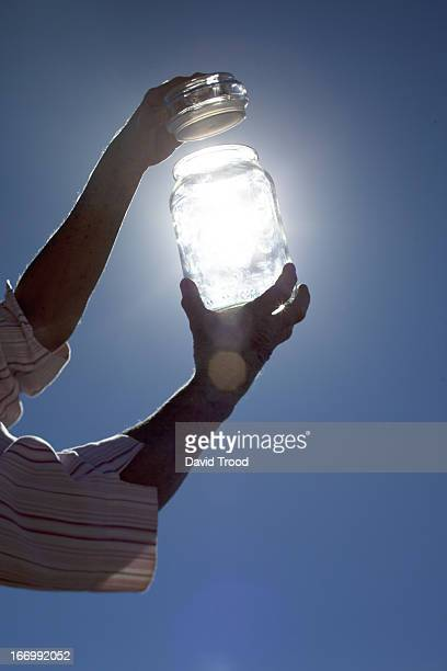 collecting sunlight in a bottle. - human arm stock pictures, royalty-free photos & images