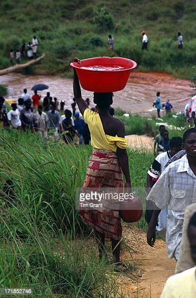 Collecting Water - a dangerous activity in Angola. A woman waits for a break in the line before she can pass on the only safe path to town. The area...