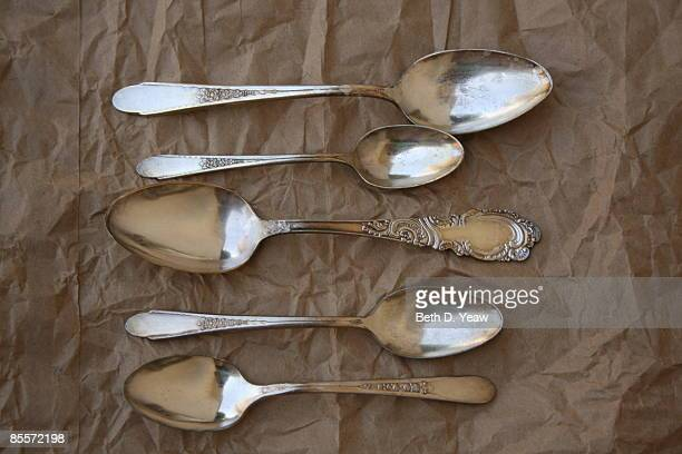 A collection of 5 antique spoons on brown paper