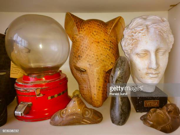collection of a hand carved indigenous mask, gum-ball machine, abstract stone figure, aztec head and the bust of a hygeia, greek goddess of good health, displayed on a shelf. - aztec mask stock pictures, royalty-free photos & images