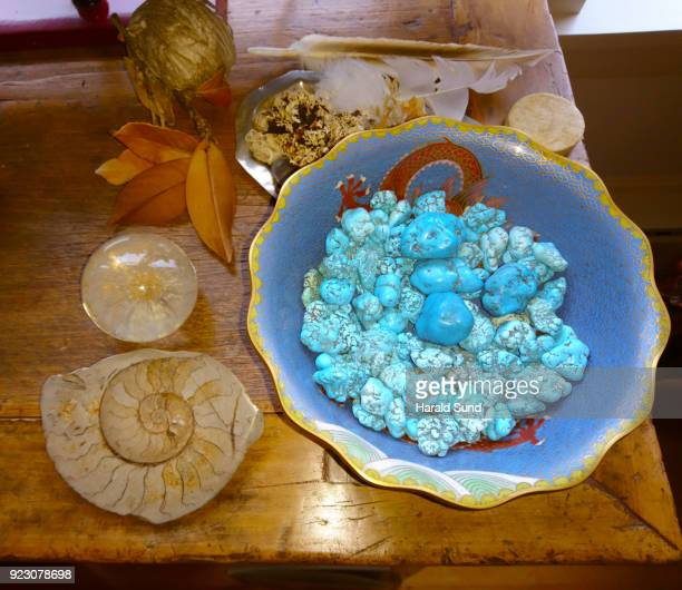 Collection of a nautilus fossil, glass sphere, beehive, dried leaves and a Chinese cloisonné bowl filled with turquoise nuggets displayed on a wood table.