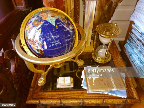 Collection of a world globe, books and a brass hour glass displayed on a bamboo table.