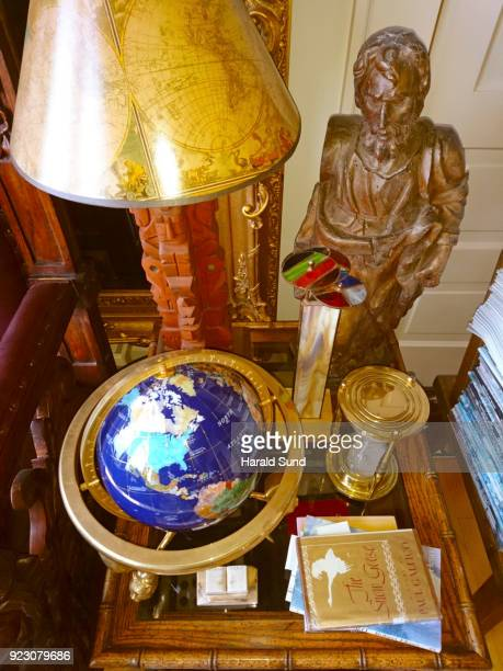 Collection of a world globe, books, kaleidoscope, lamp with map of the earth shade, brass hour glass and a hand carved religious figure displayed on a bamboo table.