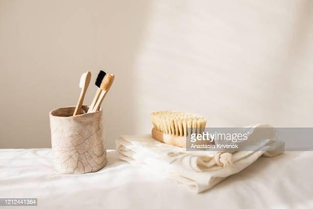 collection of assorted kitchen and bathroom tools, organic sponges and brushes, natural soap, wood toothbrushes, linen napkin and other ecological products on beige background. set of zero waste cleaning products. eco friendly concept - umweltschutz stock-fotos und bilder