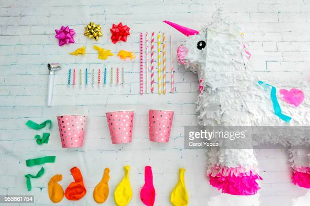 collection of birthday party objects in white with unicorn pinata - pinata stock pictures, royalty-free photos & images