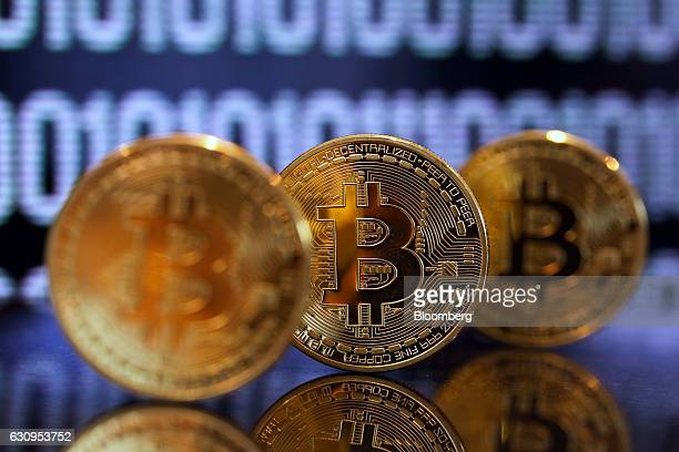 A collection of bitcoin tokens stand in front of an illustration of binary code in this arranged photograph in London UK on Wednesday Jan 4 2017 The...