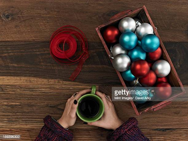A collection of blue, red and silver ornaments and red ribbon in a box on a wooden board. A hand curled around a cup of coffee. Taking a break.