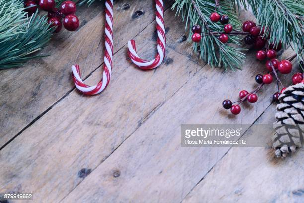 Collection of Christmas ornaments: Sweet Christmas candy cane and pine cone framed with fir tree branches and seed mistletoe on rustic wooden background. Selective focus and copy space